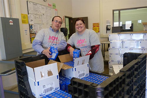 volunteers packing food into boxes - Give Food
